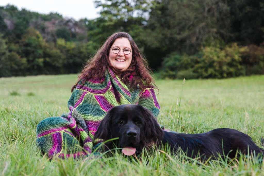 Stefanie Wagner sitzt mit ihrem Hund in einer Wiese