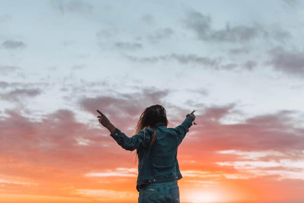 Frau hebt ihre Hände in die Luft