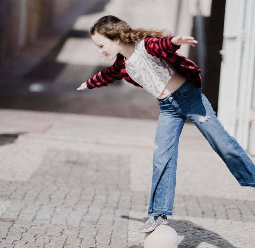 Junges Mädchen balanciert auf Straßenpfosten aus Stein
