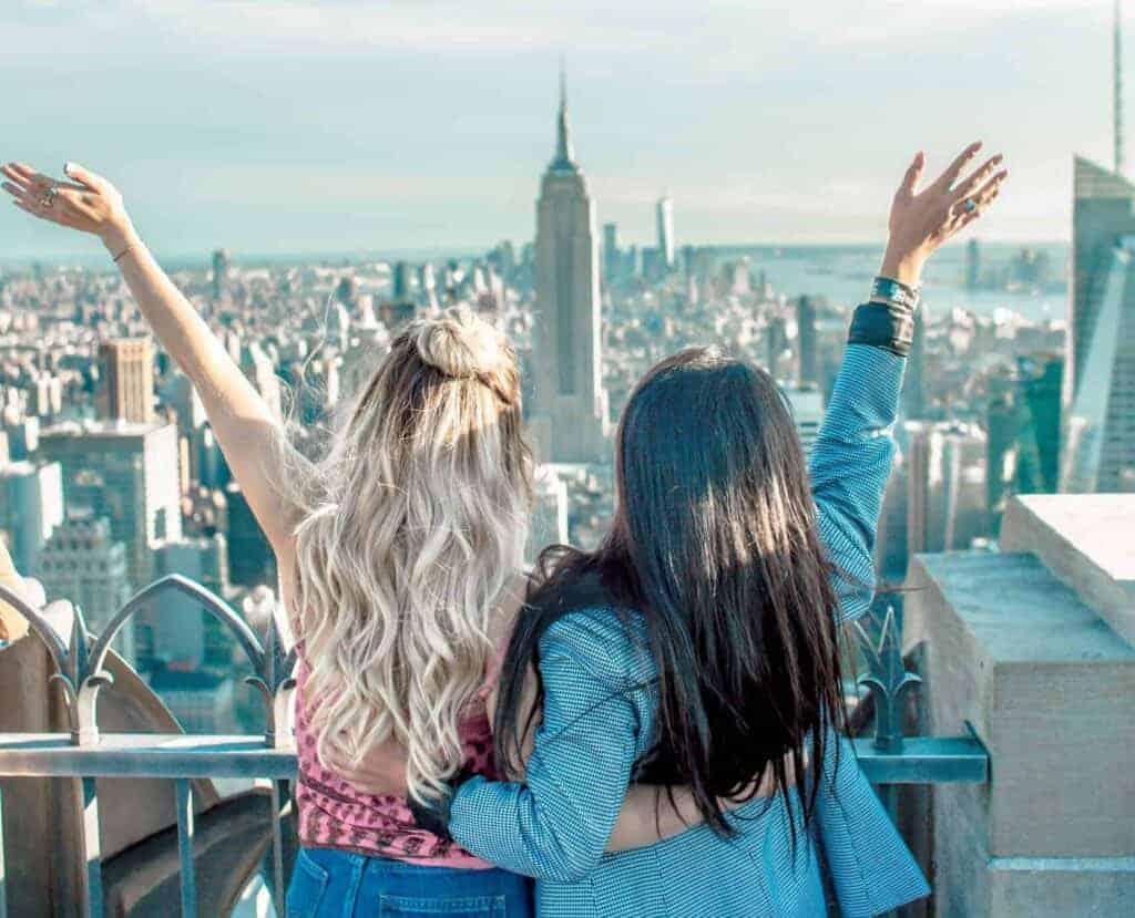 Zwei junge Frauen blicken auf Hochhäuser, umklammern sich und jubeln
