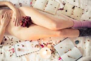 Nackter, bedeckter Frauenkörper in Bett mit Weintrauben und Blumenblättern sowie Büchern und Kerze