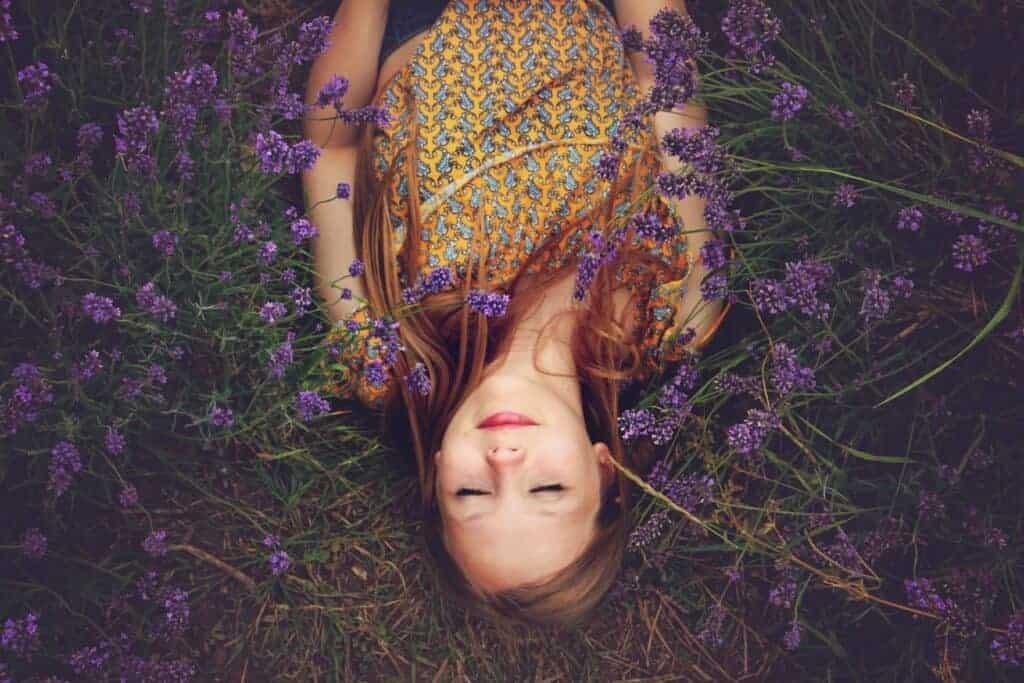 Junge Frau schläft auf einer Blumenwiese