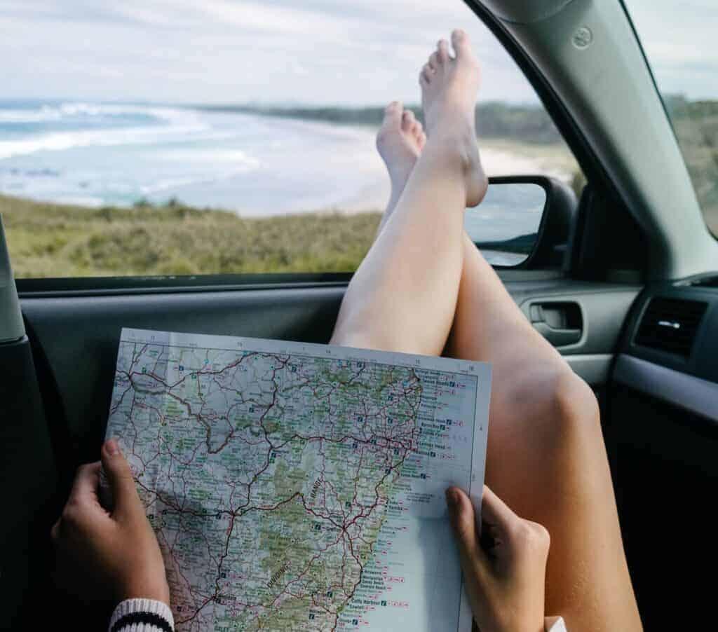 Beine hängen aus dem Autofenster mit einer Landkarte auf dem Schoß