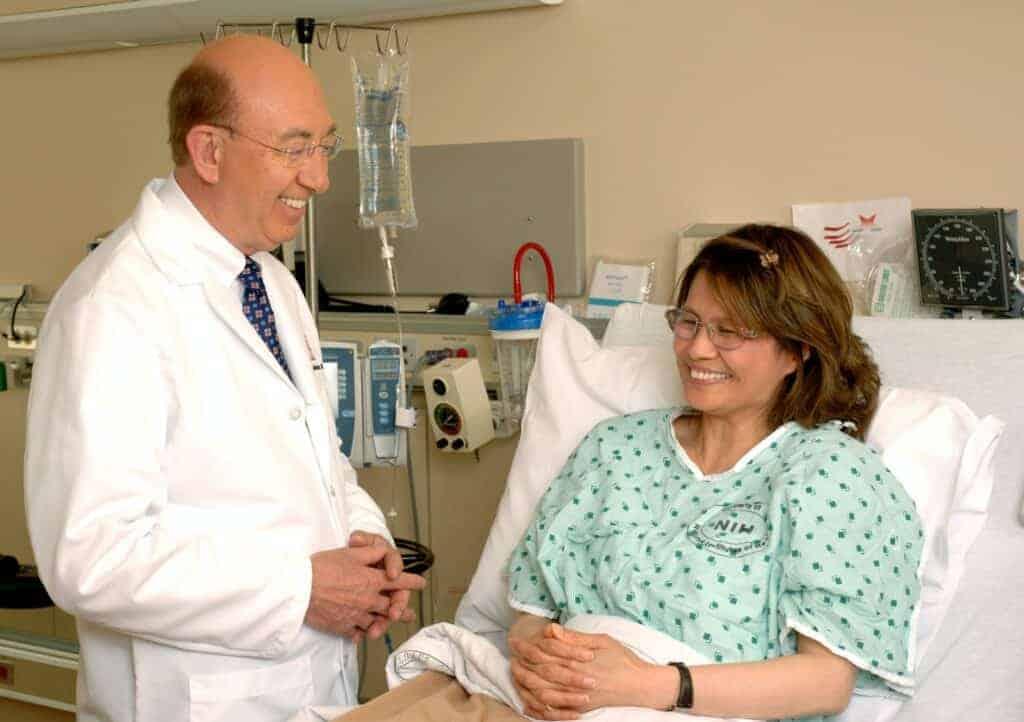 Arzt neben Frau im Krankenbett